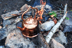 Metal camp kettle hanging over the campfire. Metal camp kettle hanging over the coals campfire royalty free stock photos