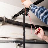 Handyman lubricates a garage door opener release leaver with a can of oil. Metal can of oil is used to lubricate a release leaver for a garage door royalty free stock image