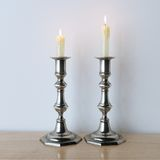Metal candelabras with wax candles on wooden background. Royalty Free Stock Photos
