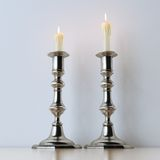 Metal candelabras with wax candles on wooden background. Royalty Free Stock Photo