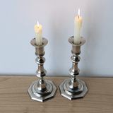 Metal candelabras with wax candles on wooden background. Stock Photo