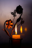 Metal candlestick in the form of flowers with butterflies with a burning candle. Bronze candlestick in the form of flowers with butterflies with a burning candle Royalty Free Stock Photo