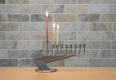 A metal candlestick for the  Hanukkah celebration stands with lit candles on the table against the backdrop of a brick wall. A metal candlestick for the Hanukkah Royalty Free Stock Images