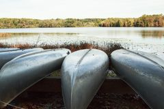 Metal Canoes resting on a boat rack near the lake. On a sunny day Royalty Free Stock Photo
