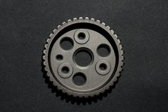 Metal car cogwheel on black background. Metal car cogwheel a part of timing chain with holes in it on black background stock image