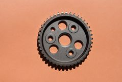 Metal cogwheel on pink background. Metal car cogwheel a part of timing chain with holes in it on pink background stock images