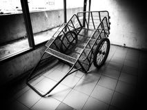 Metal cart cornered. A metal car with a flat tire left by a window Stock Photos
