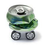 Metal Car Recycling Sustainability. A crushed aluminium can with car wheels on a white background Royalty Free Stock Image