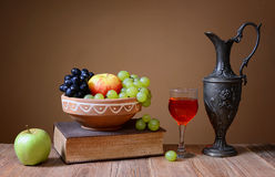 Metal carafe fruits and books Royalty Free Stock Images