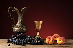 Metal carafe, grapes and peaches Royalty Free Stock Photo