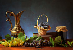 Metal carafe and plums in a wicker basket Royalty Free Stock Photography
