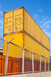 Metal cargo containers are stacked under blue cloudy sky. Metal Industrial cargo containers are stacked under blue cloudy sky. Vertical photo Stock Image