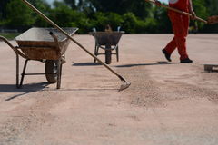 Metal cart with rakes on construction site. In the background is worker with a shovel. Photo was taken on a construction site near football stadium Spartak Stock Photos