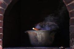 Metal cauldron slowly cooking Stock Image