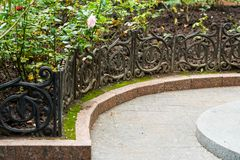 Metal a cerca de uma cama de flor em um verão imagem de stock