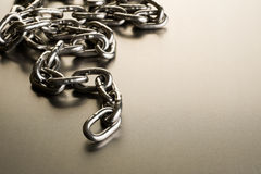 Metal chain. A metal chain on a steel background, the first few links in focus Stock Images