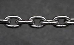 Metal Chain. Silver Metal Chain With Multiple Linked Components In Front Of A Grey Blurred Background Stock Photo