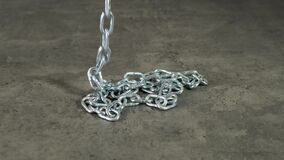 Metal chain falls on the black table. Close up.