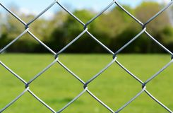 Metal chain-link fence. Metal chain link fencing in selective focus. Beyond the secure fence lies an empty green field, lined by trees Royalty Free Stock Photography