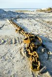Metal chain lying on the beach. Long chain on the the sand, empty horizon, seascape Stock Image