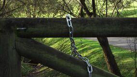 A metal chain on a mossy log wooden gate in the countryside.