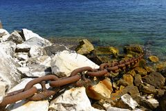 Metal chain secures a distant ship to the shore. Royalty Free Stock Photos