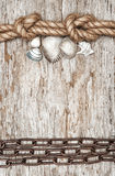 Metal chain, ship rope and seashells on the old wood Royalty Free Stock Photo