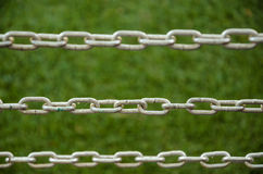 Metal chains on green background. Stock Photo