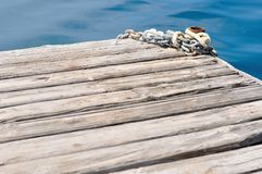 Metal chains and mooring bollard on wooden pier Stock Images
