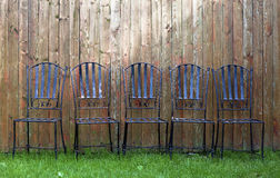 Metal chair in grass. 5 chairs in the grass with plank fence Stock Images