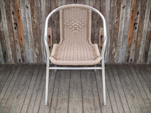 Metal chair with woven seat on old wooden floor Royalty Free Stock Photo