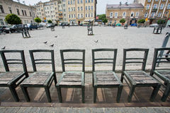 Metal chairs on cobbled street in art installation of city Stock Photo