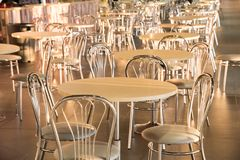 Metal chairs with high backs and tables in the morning sun in th. Metal chairs with high backs and square tables in the morning sun in the cafe royalty free stock photography