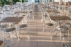 Metal chairs with high backs and tables in the morning sun in th. Metal chairs with high backs and square tables in the morning sun in the cafe stock photography