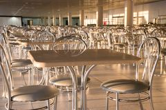 Metal chairs with high backs and tables in the morning sun in th. Metal chairs with high backs and square tables in the morning sun in the cafe stock photo