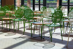 Metal chairs and wooden tables in the hall Royalty Free Stock Photos