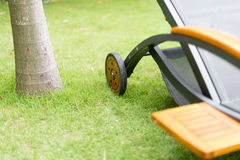 Metal chaise-longue on green grass near tree. Detail of empty metal chaise-longue with wheels on green grass near palm. Relaxation and sunbathing on hot day stock photos