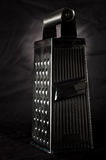Metal cheese grater. Stylish parmesan grater, isolated on black Royalty Free Stock Photo