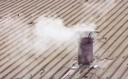 Metal chimney on copper roof with smoke - image with copy space Stock Image