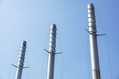 Metal chimneys with antivortic spiral and blue sky in the background Stock Photography