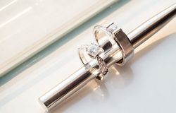 metal chopstick insert within two diamond wedding rings for groom and bride on white background stock photo