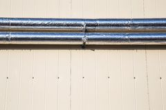 Metal chrome pipes on siding wall Royalty Free Stock Photos
