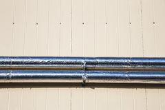 Metal chrome pipes on siding wall Stock Photo