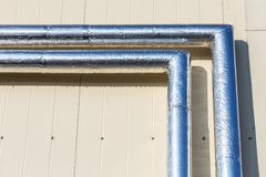 Metal chrome pipes on siding wall Stock Photos