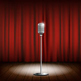 Metal chrome retro microphone on a stand. Scene with a red curta Royalty Free Stock Photo