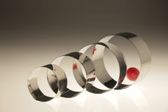 Metal chrome rings. Of different diameters are on the table. There is the red dot, the focus, which is reflected in the rings Royalty Free Stock Images