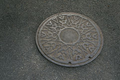 Metal circle of drain water on pavement Royalty Free Stock Photos