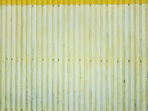 Metal cladding wall design old lemon color background texture with screws in the lower part. Stock Photo