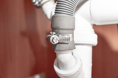 Metal clamp for connection of dishwasher drain hose under kitchen sink close up royalty free stock photos