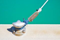 Metal cleat for mooring boats, bolted to the ground, with rope and shock absorber spring.  stock images